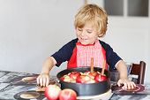 picture of pie-in-face  - Adorable little boy helping and baking apple pie in home - JPG