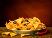 picture of nachos  - still life with baked nachos cheese olives and chili peppers - JPG