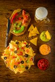 stock photo of nachos  - nachos on a plate with salsa cheese and guacamole dip and beer mug - JPG