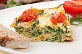 picture of kale  - Closeup of plate with one piece of fresh made frittata bread and tomatoes - JPG