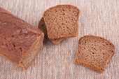 image of fresh slice bread  - Sliced fresh bread on the tablecloth on the kitchen table - JPG