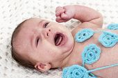 picture of cry  - Little newborn baby lying on a white knitted scarf and cries - JPG