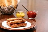 pic of condiment  - Grilled brats on a stacked on a plate ready to serve with condiments ketchup and mustard and buns - JPG
