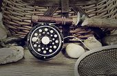 foto of fly rod  - Vintage concept with grain of a wet antique fly fishing reel rod landing net artificial flies and rocks in front of creel with rustic wood underneath - JPG