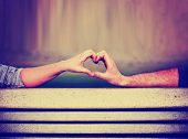 picture of bench  -  two people making a heart shape with their hands on a bench toned with a retro vintage instagram filter  app or action  - JPG