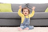 foto of sofa  - Playful baby girl sitting on the floor next to a modern sofa and gesturing happiness isolated on white background - JPG