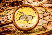 picture of treasure map  - Vintage magnifying glass lies on the ancient map of the North Pole  - JPG
