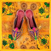 image of flea  - Colorful ethnic shoes on yellow Rajasthan cushion cover on flea market in India - JPG