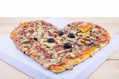 picture of olive shaped  - Heart shaped pizza on a wooden table - JPG