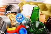 stock photo of segregation  - Recyclable garbage consisting of glass plastic metal and paper on white background - JPG