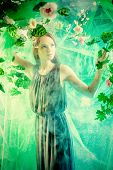 stock photo of tropical plants  - Beautiful young woman  among tropical plants and flowers - JPG