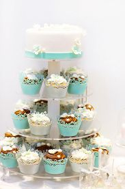 image of icing  - Wedding cake and cupcakes in brown and cream in blue white and brown. Icing with cream marzipan details of cake.