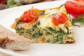 stock photo of baby goat  - Closeup of plate with one piece of fresh made frittata bread and tomatoes - JPG