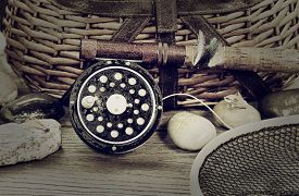 image of fly rod  - Vintage concept with grain of a wet antique fly fishing reel rod landing net artificial flies and rocks in front of creel with rustic wood underneath - JPG