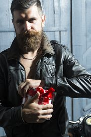 picture of moustache  - Attractive unshaven man with beard and moustache in brown leather jacket and chain opening round red white striped present box with ribbon bow standing on grey wooden background vertical picture - JPG