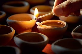 picture of diya  - Hand holding a matchstick lighting diya lamps during diwali celebration - JPG