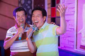 picture of karaoke  - Senior male friends singing in karaoke bar - JPG