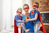 Mother and her children playing together. Girls and mom in Superhero costumes. Mum and kids having f poster