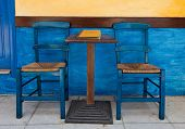 Blue Chairs On A Greek Cafe