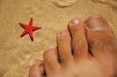 Red Star And Toes On Sand