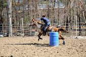 stock photo of barrel racing  - A young woman turns around a barrel and races to the finish line - JPG