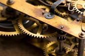 Clockwork. Old brass gears of clock mechanism. Shallow depth of field. poster