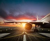 Detail of commercial airplane staying at the runway, wing and jet engine. Modern cityscape silhouett poster