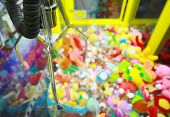 Capture device for soft toys on background of heap of colorful soft toys in arcade machine