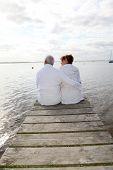 Senior couple in bathrobe sitting on a pontoon