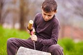 Boy Sculpting In A Log With A Chisel