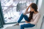 Winter depressed sad girl lonely by home window looking at cold weather upset unhappy. Bad feelings  poster