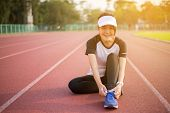 Runner Asian Woman Tying A Shoelaces On Running Shoes,women Athletic Preparing For Jogging Or Run Ou poster