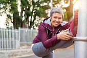 Smiling retired woman listening to music while stretching legs outdoors. Senior woman enjoying daily poster