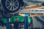 Modern Auto Service And Caucasian Car Mechanic. Broken Vehicles On A Lifts. Automotive Industry. poster