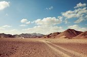 Safari and extreme travel in Africa. Drought  mountain landscape with dust off road in offroad car e poster