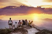 Big Group Of Friends Stands On Mountain Top And Looks At Beautiful Sunset. Travel With Friends Conce poster