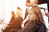 Bearded Barber Makes Curls On Hair Of Beautiful Little Girl With Hair Curler. Female Stylist Makes S poster