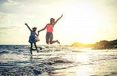 Happy Loving Family Of Mother And Daughter Jumping In The Water At Sunset On The Beach - Mom With He poster