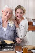picture of pancake flip  - Mother and daughter cooking crepes together - JPG