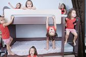 Many Clone Little Girls On Bund Bed In Child Room In Domestic Life. Identical Child Crowd. Child Omn poster
