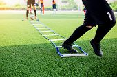 Young Boy Soccer Players Jogging And Jump Between Ladder Drills For Football Training poster
