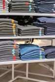 Neatly Folded Clothes. Rack Of Clothes With Warm. Wooden Cabinet With A Stack Of Sweaters. Coloured  poster
