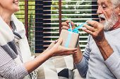 Senior Man Giving Gift Box To Wife And Talking Together Sitting On Sofa In Living Room At Home.retir poster