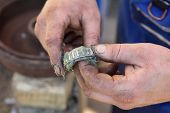 stock photo of friction  - Mechanic lubricate a roller bearing with lithium grease - JPG