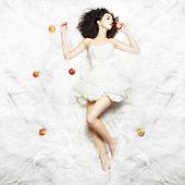 stock photo of love bite  - Caucasian girl sleeping on white fabric after eating an apple - JPG