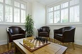 Study room with three leather armchairs and chess board