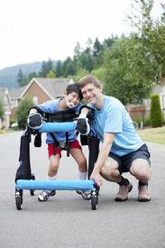 image of street-walker  - Father kneeling next to disabled son standing in walker  - JPG