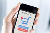 foto of cart  - Mens hand holding modern apple iphone with online shopping application on a screen - JPG