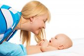 image of tickle  - Mommy tickling little baby boy laying with him in the bed with big smile on her face - JPG