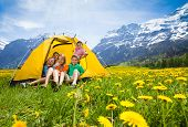 stock photo of tent  - Group of kids boys and girls sitting together in the tent in dandelion field - JPG